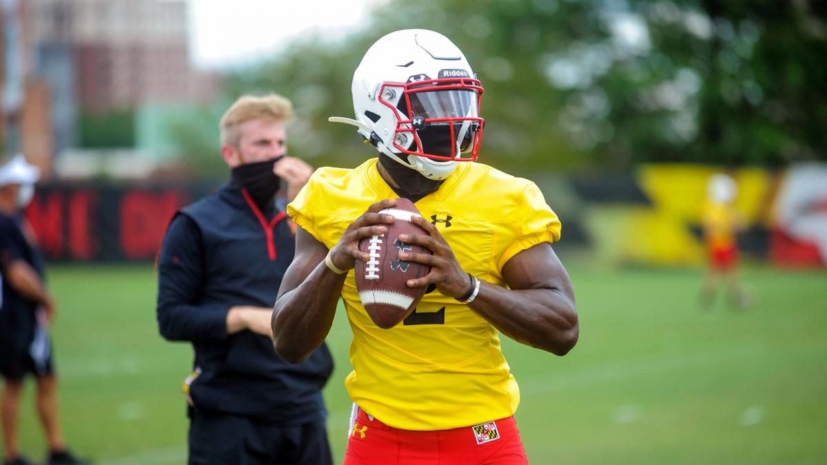 Maryland football player in yellow and red Maryland practice uniform, preparing to throw the ball