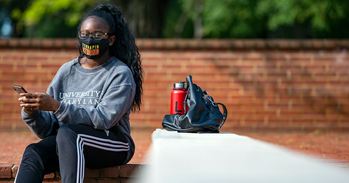 Young lady wearing a TerrapinSTRONG Face Covering and Terp sweatshirt