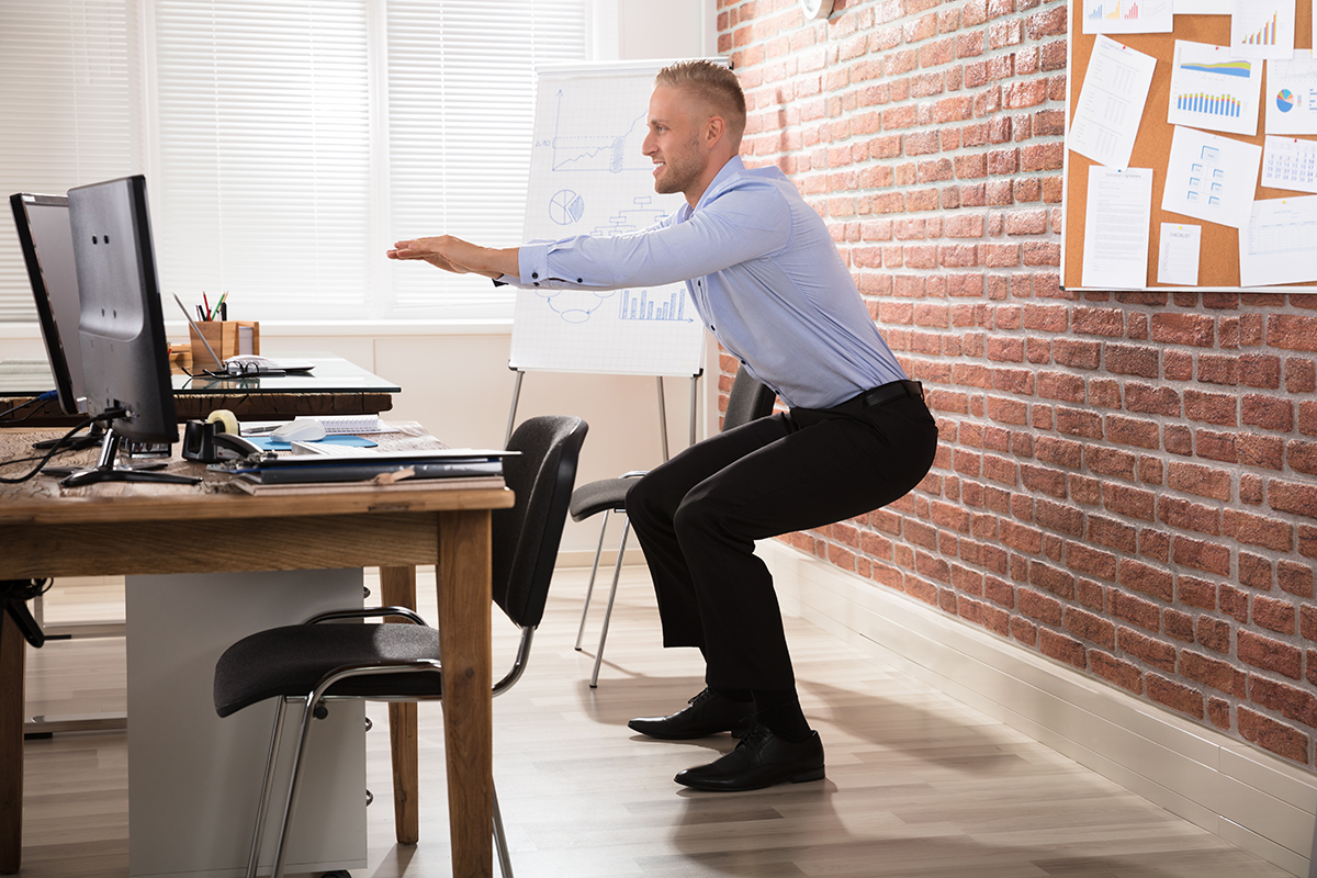 Photo of Man Squatting at Desk