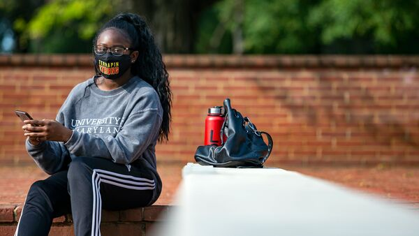 A young woman sits outside wearing a Terrapin Strong mask and a Maryland sweatshirt