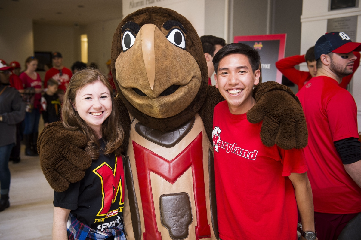 Testudo with arms around two Maryland alum