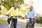 Elderly couple smiling while bike riding