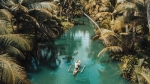Man kayaking on a river, surrounded by palm trees.
